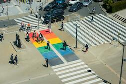 Pedestrians and cyclists crossing on a zebra crossing painted in the colors of the rainbow ...